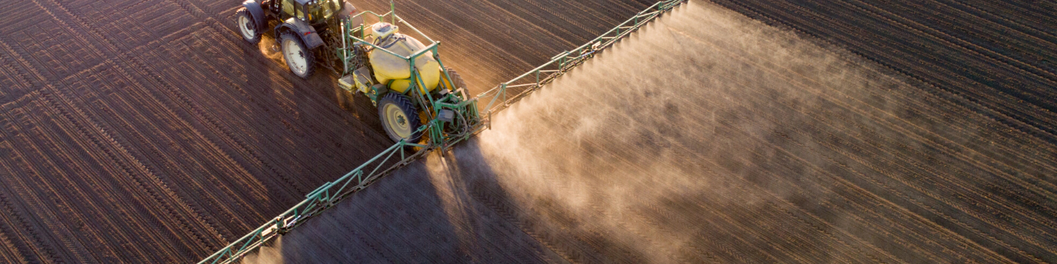 Tractor spraying agrochemicals in field