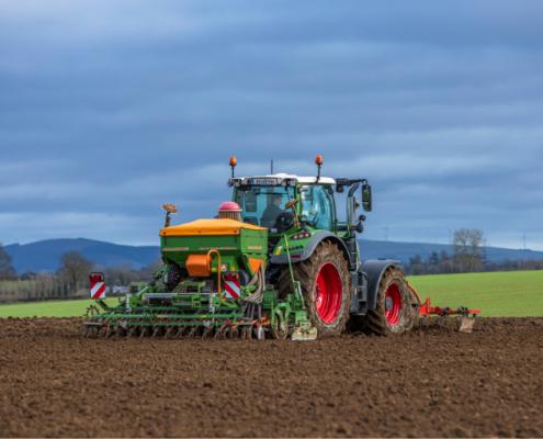 Tractor reseeding grass in field